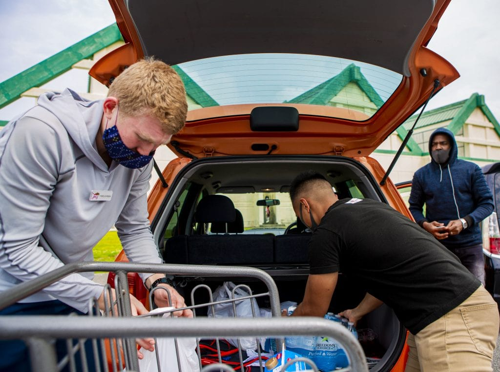 Volunteers loading groceries. grocery shopping habits